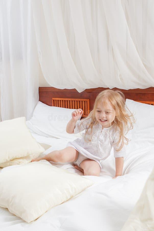 Ευτυχές μικρό κορίτσι σε ένα κρεβάτι στοκ φωτογραφίες