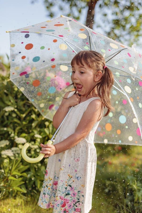 Ευτυχές μικρό κορίτσι στον κήπο κάτω από τη θερινή βροχή με μια ομπρέλα στοκ εικόνα