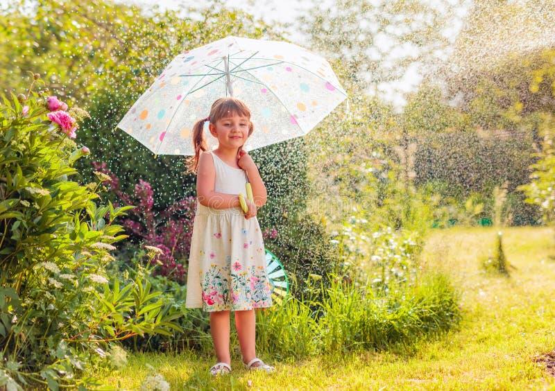 Ευτυχές μικρό κορίτσι στον κήπο κάτω από τη θερινή βροχή με μια ομπρέλα στοκ εικόνες