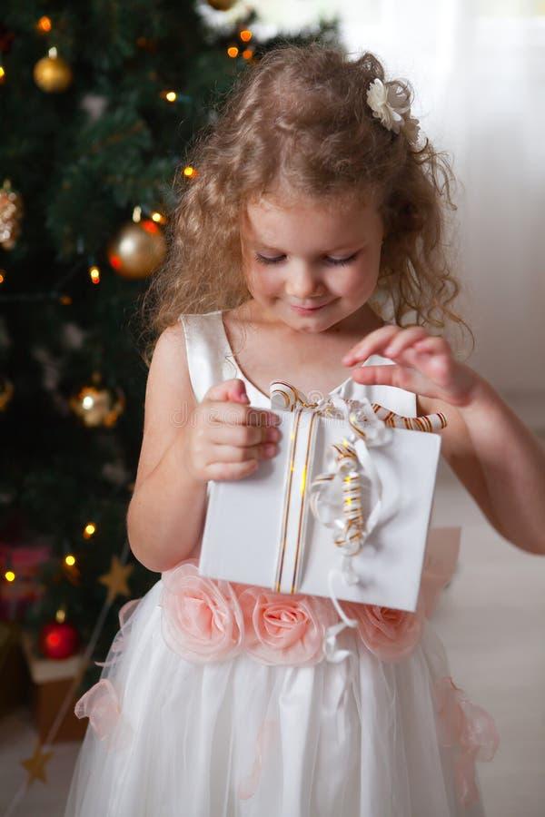 Ευτυχές μικρό κορίτσι στο άσπρο φόρεμα που κρατά ένα κιβώτιο με ένα δώρο στοκ εικόνα