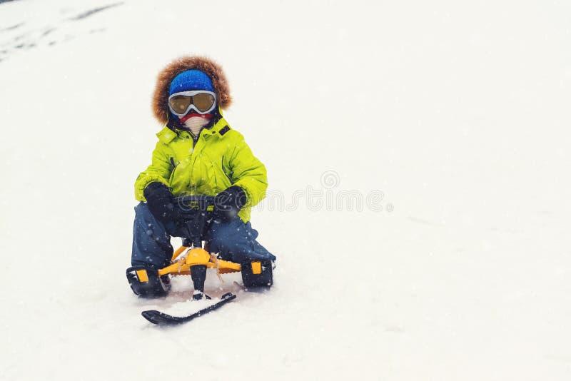 Ευτυχές μικρό παιδί που απολαμβάνει το γύρο ελκήθρων Χειμερινές δραστηριότητες παιδιών Παιδιών Παιδί που φορά τα θερμά ενδύματα σ στοκ εικόνα