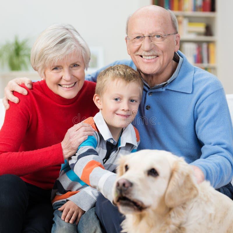 Ευτυχές μικρό παιδί με τους ηλικιωμένους παππούδες και γιαγιάδες του στοκ εικόνα