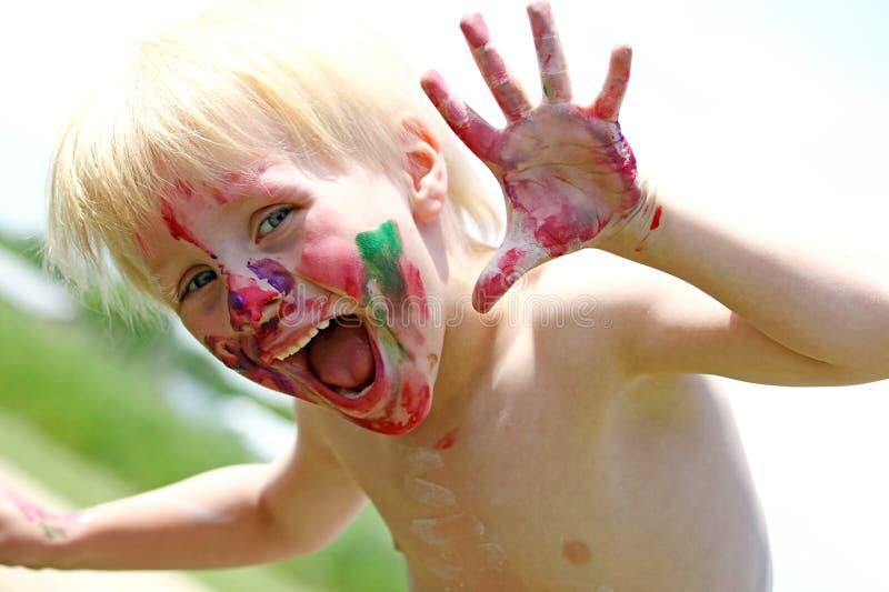 Ευτυχές μικρό παιδί με το ακατάστατο χρωματισμένο πρόσωπο στοκ εικόνες