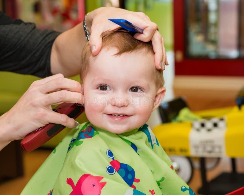 Ευτυχές μικρό παιδί που παίρνει το πρώτο κούρεμά του στοκ φωτογραφία