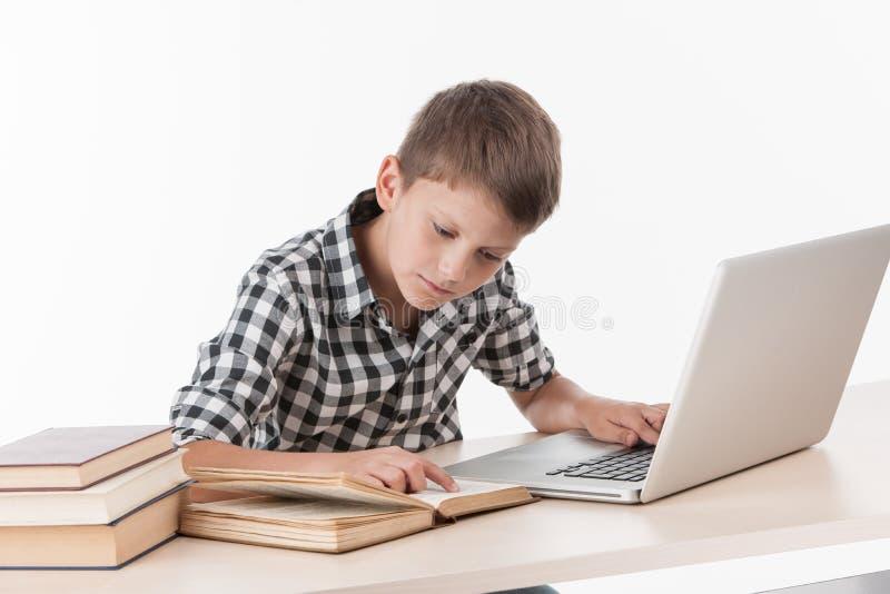 Ευτυχές μικρό παιδί που χρησιμοποιεί το lap-top στον πίνακα στοκ εικόνες