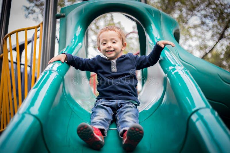 Ευτυχές μικρό παιδί στη φωτογραφική διαφάνεια παιδικών χαρών στοκ εικόνες