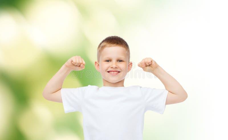 Ευτυχές μικρό παιδί στους άσπρους δικέφαλους μυς κάμψης μπλουζών στοκ εικόνα