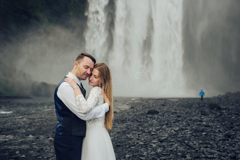 Ευτυχές μοντέρνο χαμογελώντας ζεύγος που περπατά και που φιλά στην Ισλανδία, επάνω στοκ φωτογραφία