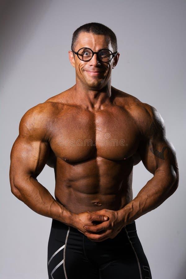Ευτυχές μυϊκό άτομο με έναν γυμνό κορμό και αστεία γυαλιά στοκ φωτογραφίες