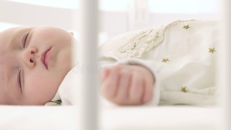 Ευτυχές μωρό ένας ύπνος στο κρεβάτι στοκ φωτογραφίες