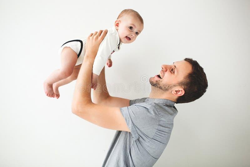 Ευτυχές μωρό εκμετάλλευσης πατέρων απομονωμένη χεριών από πάνω στο υπόβαθρο στοκ φωτογραφίες