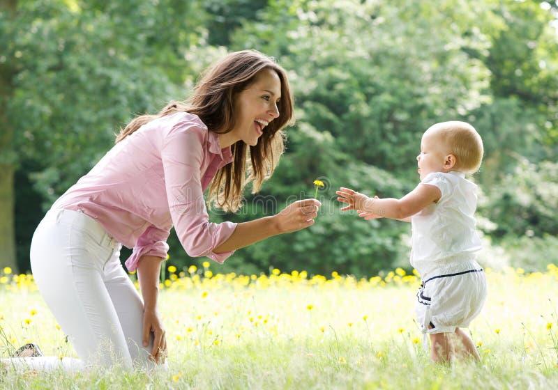 Ευτυχές μωρό διδασκαλίας μητέρων για να περπατήσει στο πάρκο στοκ εικόνα