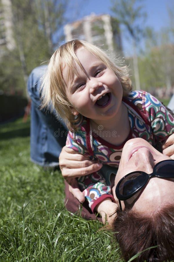 Ευτυχές μωρό και mom να βρεθεί στη χλόη στοκ εικόνα με δικαίωμα ελεύθερης χρήσης