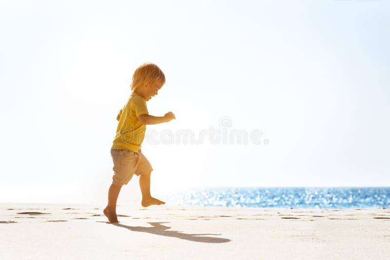 Ευτυχές μωρό που περπατά στη μόνη παραλία στοκ φωτογραφία
