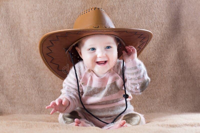 Ευτυχές μωρό που φορά την εξάρτηση κοριτσιών αγελάδων με το μεγάλο καπέλο στοκ εικόνα με δικαίωμα ελεύθερης χρήσης