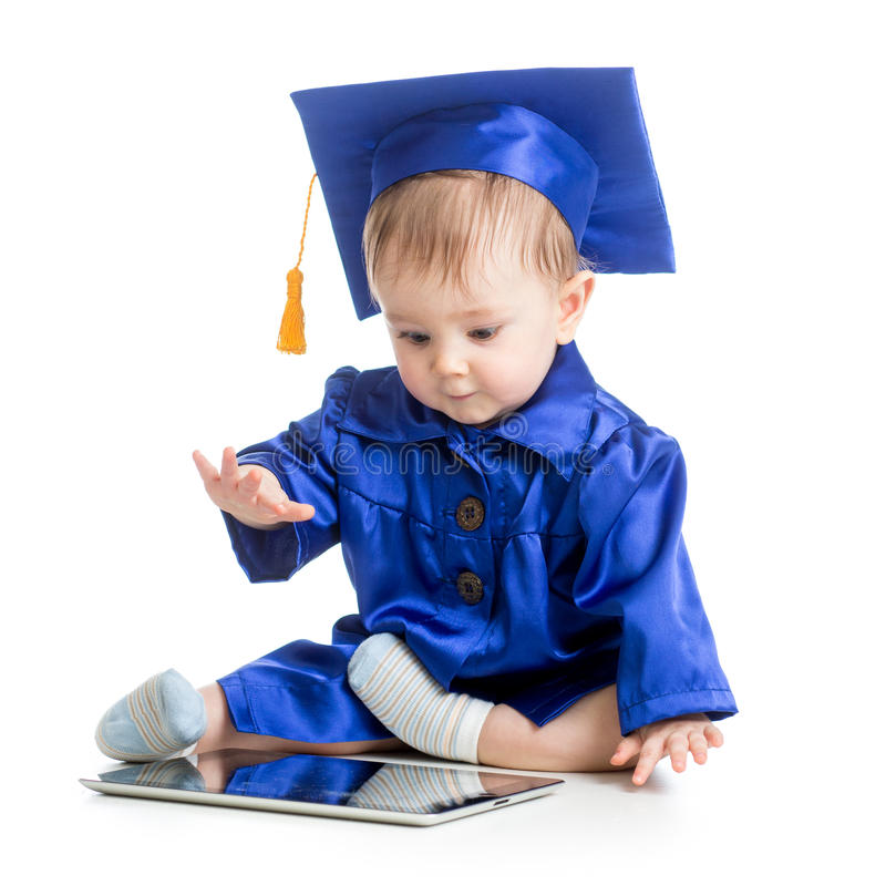 Ευτυχές μωρό στα ενδύματα ακαδημαϊκών με το lap-top στοκ φωτογραφίες