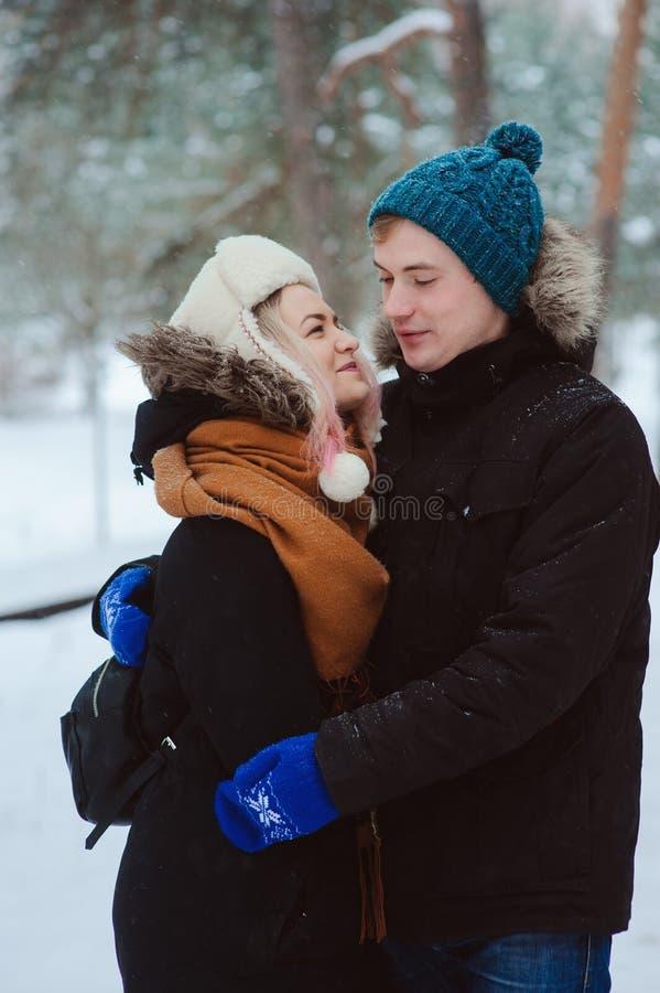 ευτυχές νέο αγαπώντας ζεύγος που περπατά στο χιονώδες χειμερινό δάσος, που έχει τη διασκέδαση και τα φιλιά στοκ φωτογραφία με δικαίωμα ελεύθερης χρήσης