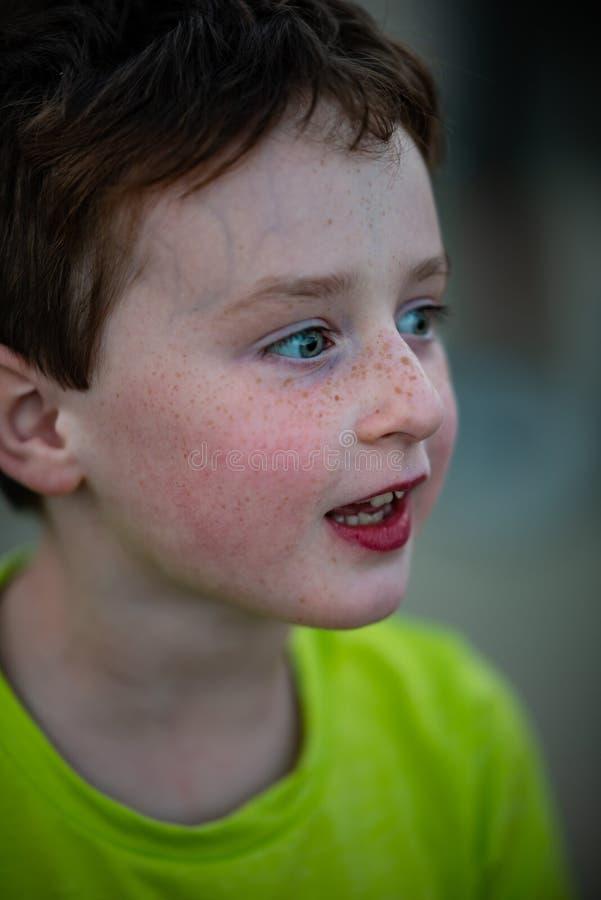 Ευτυχές νέο αγόρι που έχει τη διασκέδαση στο γύρο διασκέδασης θαλασσίων περίπατων στοκ εικόνα