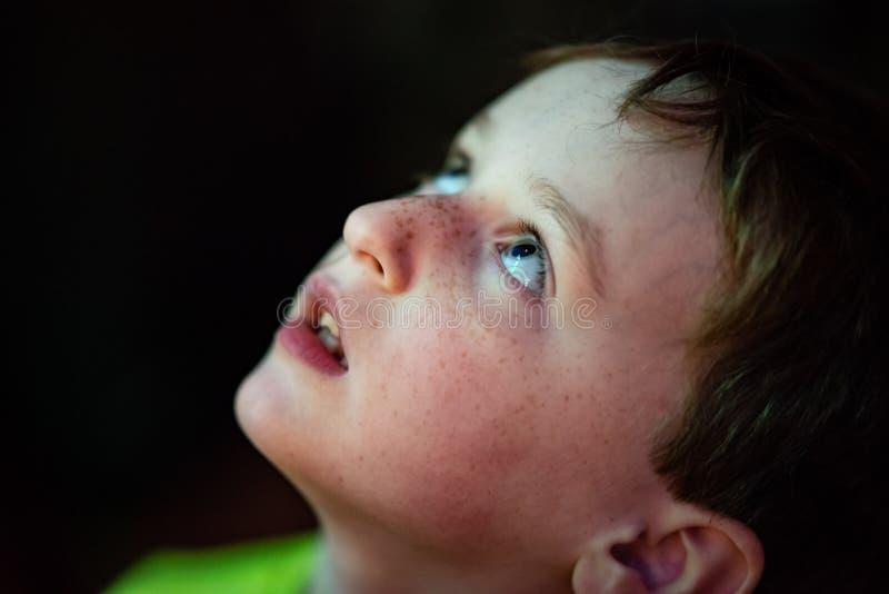 Ευτυχές νέο αγόρι που έχει τη διασκέδαση στο γύρο διασκέδασης θαλασσίων περίπατων στοκ φωτογραφία