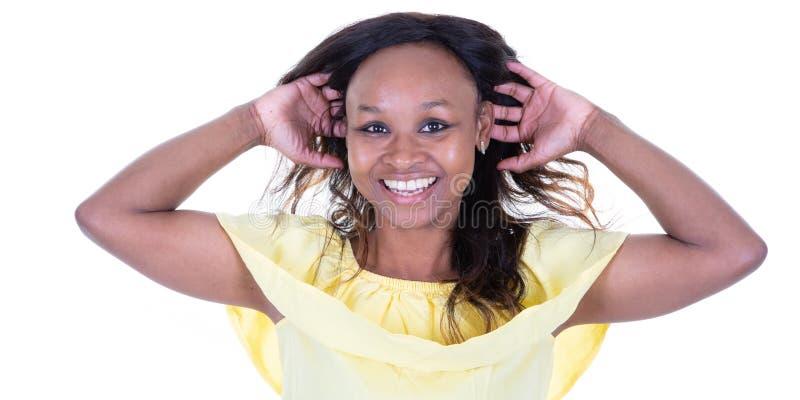 Ευτυχές νέο αμερικανικό αφρικανικό γέλιο γυναικών με τα χέρια πίσω από το κεφάλι στο άσπρο υπόβαθρο στοκ φωτογραφία