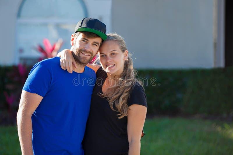 Ευτυχές νέο αμερικανικό ζεύγος με το πρώτο σπίτι στοκ εικόνες