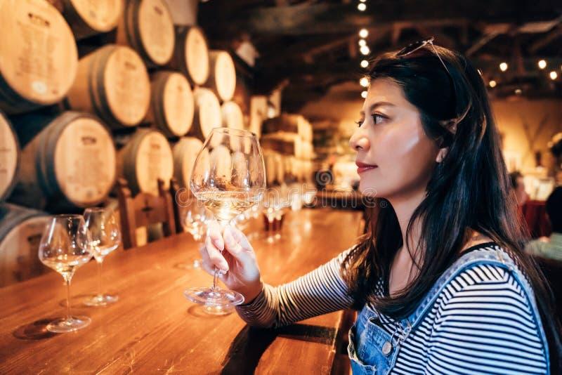 Ευτυχές νέο ασιατικό γυναικείο δοκιμάζοντας κρασί στοκ φωτογραφία