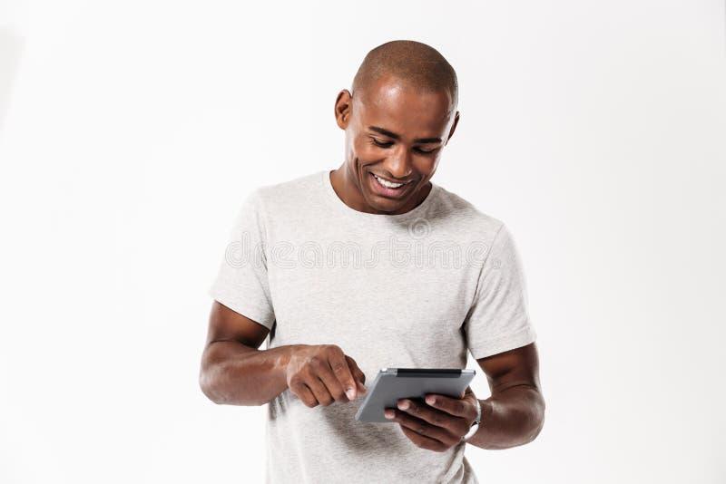 Ευτυχές νέο αφρικανικό άτομο που χρησιμοποιεί τον υπολογιστή ταμπλετών στοκ εικόνες