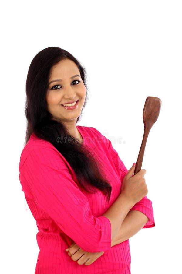 Ευτυχές νέο εργαλείο κουζινών εκμετάλλευσης γυναικών ενάντια στο άσπρο backgrou στοκ φωτογραφία