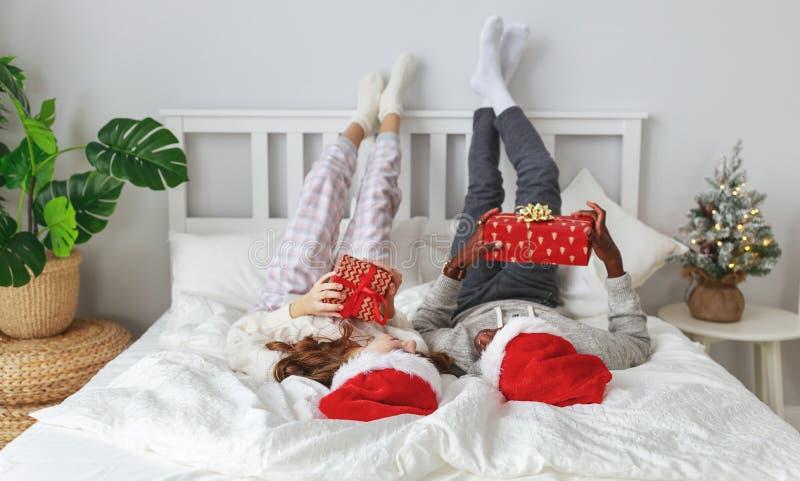 Ευτυχές νέο ζεύγος με τα δώρα στο πρωί Χριστουγέννων στο κρεβάτι στοκ φωτογραφία