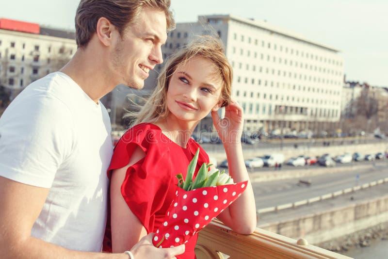 Ευτυχές νέο ζεύγος με την ανθοδέσμη στην ημερομηνία στοκ φωτογραφία