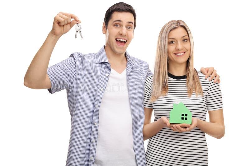 Ευτυχές νέο ζεύγος με το ζευγάρι των κλειδιών και του πρότυπου σπιτιού στοκ φωτογραφία με δικαίωμα ελεύθερης χρήσης