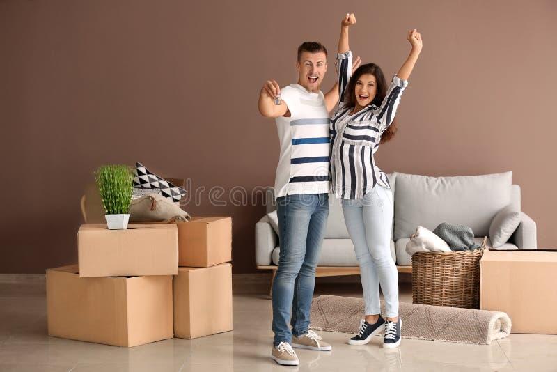 Ευτυχές νέο ζεύγος με το κλειδί από το καινούργιο σπίτι και τις περιουσίες τους στο εσωτερικό στοκ φωτογραφία με δικαίωμα ελεύθερης χρήσης
