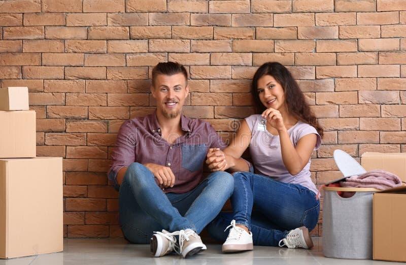 Ευτυχές νέο ζεύγος με το κλειδί από το καινούργιο σπίτι και τις περιουσίες τους που κάθεται κοντά στο τουβλότοιχο στοκ φωτογραφίες με δικαίωμα ελεύθερης χρήσης