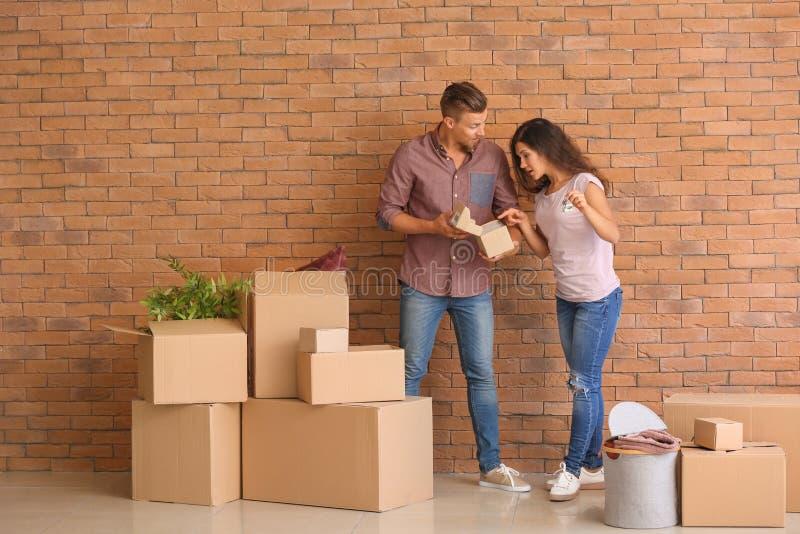 Ευτυχές νέο ζεύγος με το κλειδί από το καινούργιο σπίτι τους και περιουσίες κοντά στο τουβλότοιχο στοκ φωτογραφία με δικαίωμα ελεύθερης χρήσης