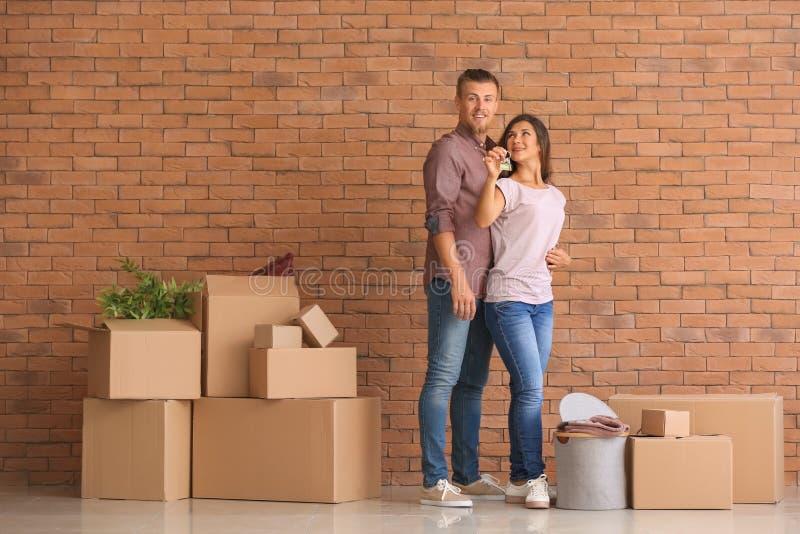 Ευτυχές νέο ζεύγος με το κλειδί από το καινούργιο σπίτι τους και περιουσίες κοντά στο τουβλότοιχο στοκ εικόνες
