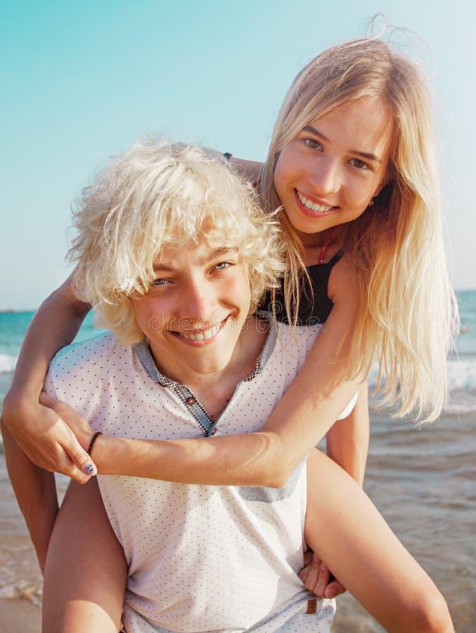Ευτυχές νέο ζεύγος που έχει τη διασκέδαση στην παραλία την ηλιόλουστη ημέρα στοκ εικόνες με δικαίωμα ελεύθερης χρήσης