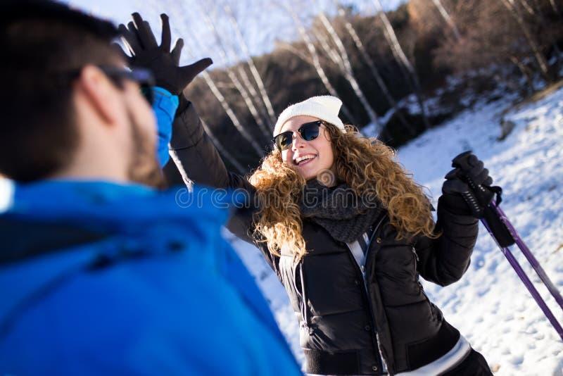 Ευτυχές νέο ζεύγος που έχει τη διασκέδαση πέρα από το χειμερινό υπόβαθρο στοκ εικόνα