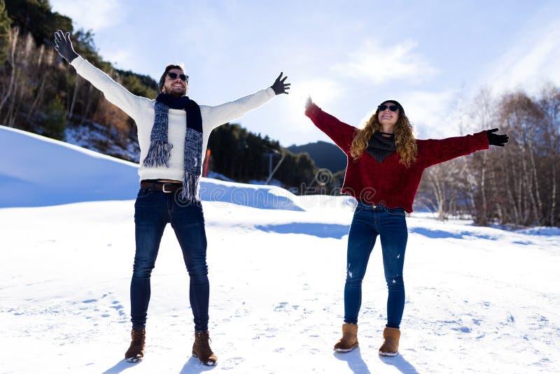 Ευτυχές νέο ζεύγος που έχει τη διασκέδαση πέρα από το χειμερινό υπόβαθρο στοκ εικόνες