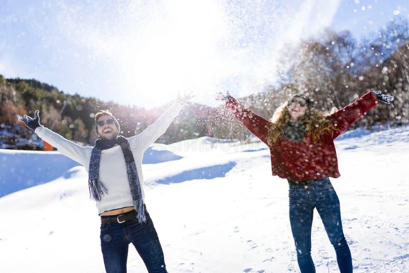 Ευτυχές νέο ζεύγος που έχει τη διασκέδαση πέρα από το χειμερινό υπόβαθρο στοκ εικόνες με δικαίωμα ελεύθερης χρήσης