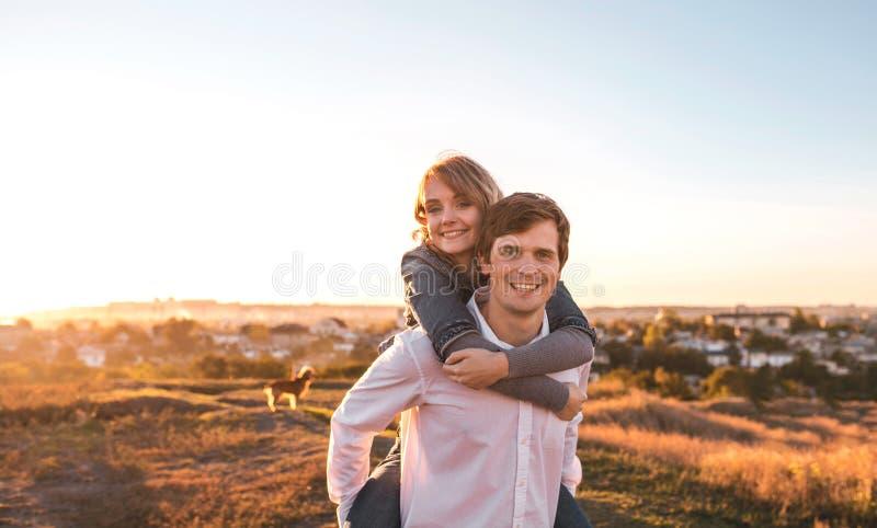 Ευτυχές νέο ζεύγος που αγκαλιάζει και που γελά υπαίθρια στοκ φωτογραφίες