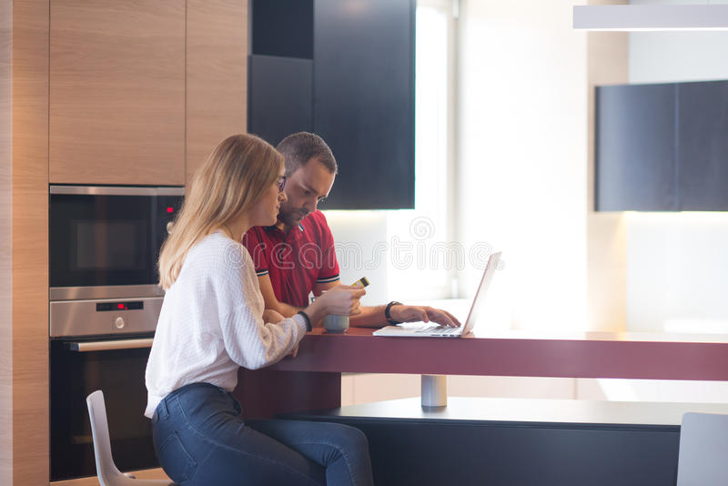Ευτυχές νέο ζεύγος που αγοράζει on-line στοκ φωτογραφία