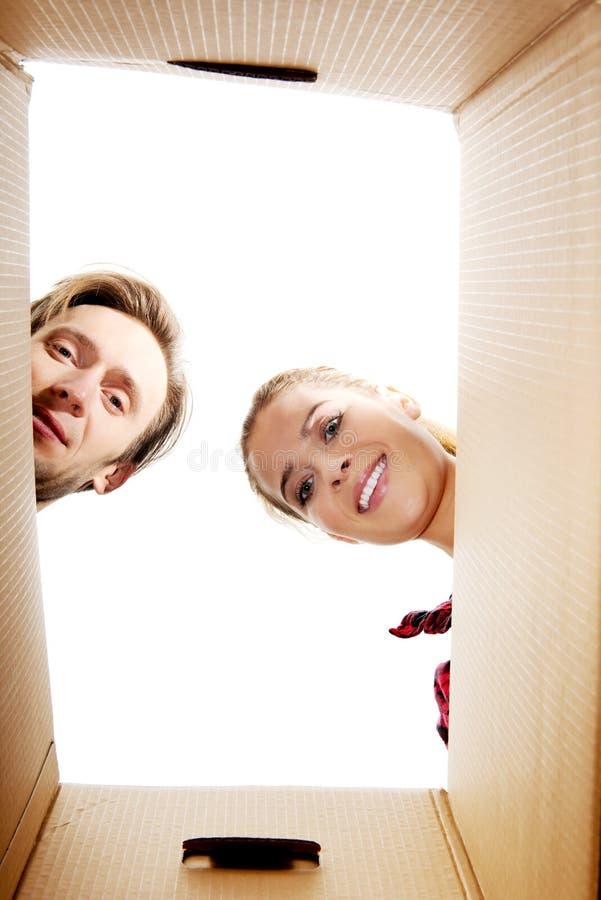 Ευτυχές νέο ζεύγος που ανοίγει ένα κιβώτιο χαρτοκιβωτίων και που κοιτάζει μέσα στοκ φωτογραφίες με δικαίωμα ελεύθερης χρήσης