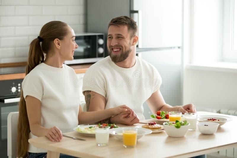Ευτυχές νέο ζεύγος που απολαμβάνει έχοντας την ετικέττα κουζινών προγευμάτων στο σπίτι στοκ εικόνα