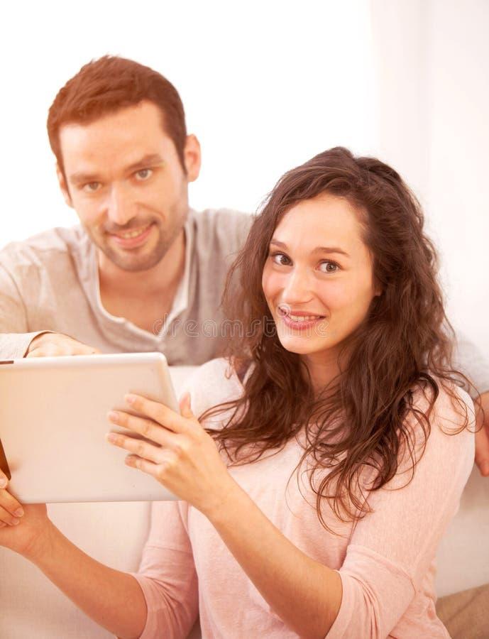 Ευτυχές νέο ζεύγος που κάνει σερφ σε μια ταμπλέτα στοκ φωτογραφία