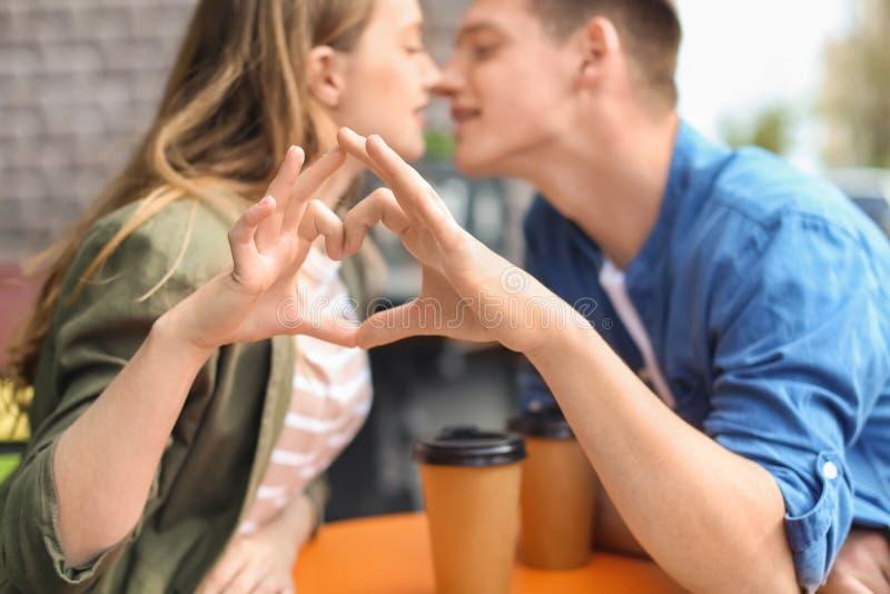 Ευτυχές νέο ζεύγος που κατασκευάζει την καρδιά με τα χέρια τους καθμένος στον καφέ οδών στοκ εικόνα
