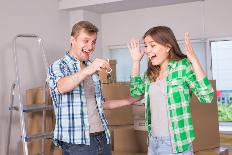 Ευτυχές νέο ζεύγος που κινείται σε ένα καινούργιο σπίτι Εγκαίνια σπιτιού, ακίνητη περιουσία και έννοια ανθρώπων στοκ εικόνες