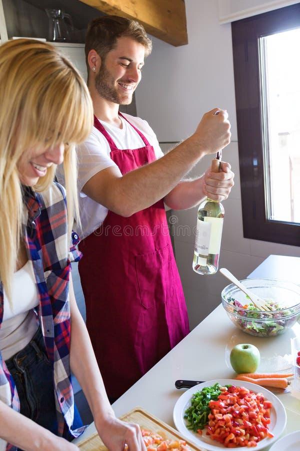 Ευτυχές νέο ζεύγος που μαγειρεύει μαζί ενώ το άτομο ανοίγει ένα άσπρο μπουκάλι κρασιού στην κουζίνα στοκ φωτογραφία