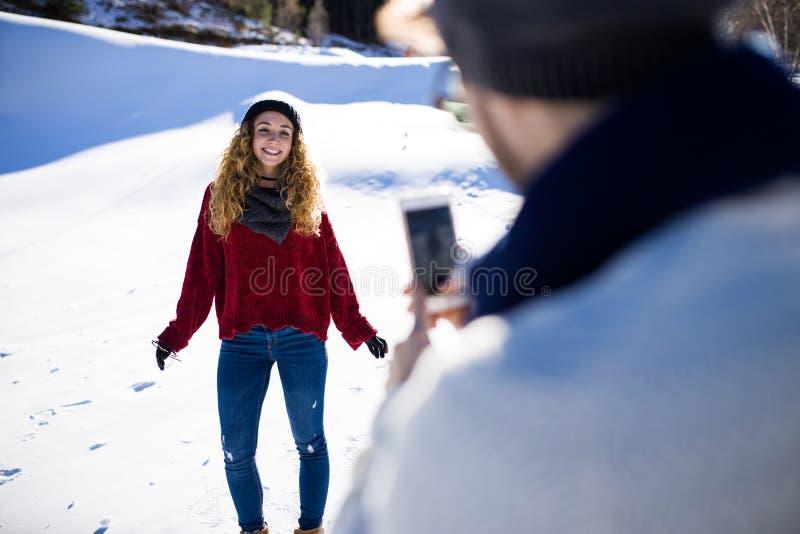 Ευτυχές νέο ζεύγος που παίρνει τις φωτογραφίες πέρα από το χειμερινό υπόβαθρο στοκ εικόνα