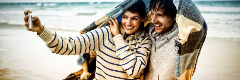 Ευτυχές νέο ζεύγος που παίρνει selfie κατά τη διάρκεια του χειμώνα στοκ εικόνες