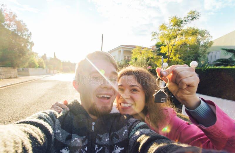 Ευτυχές νέο ζεύγος που παρουσιάζει τα κλειδιά στο νέα σπίτι και το χαμόγελό τους στοκ εικόνες
